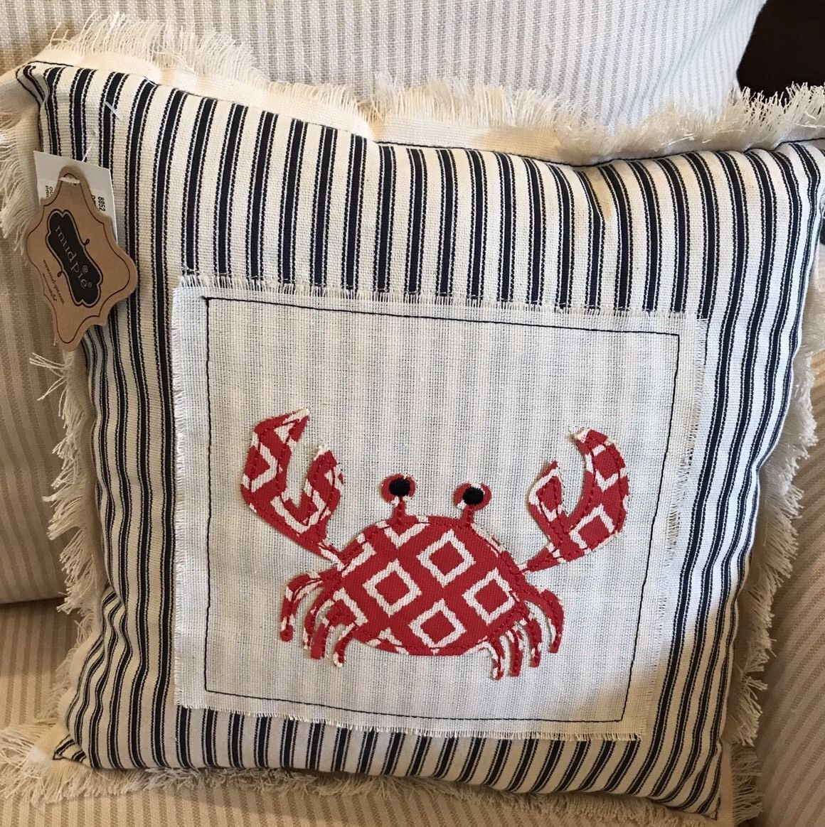 """Made of natural linen with embroidered appliqued designs and frayed edges, spot clean with damp cloth. CoastalCrab 12"""" Cotton Pillow (1) Mud Pie Measures 12"""" square. CottonCrab Pillow features top-stitched canvas layer with Navy French ticking and red crab applique.Fringe around sides. 