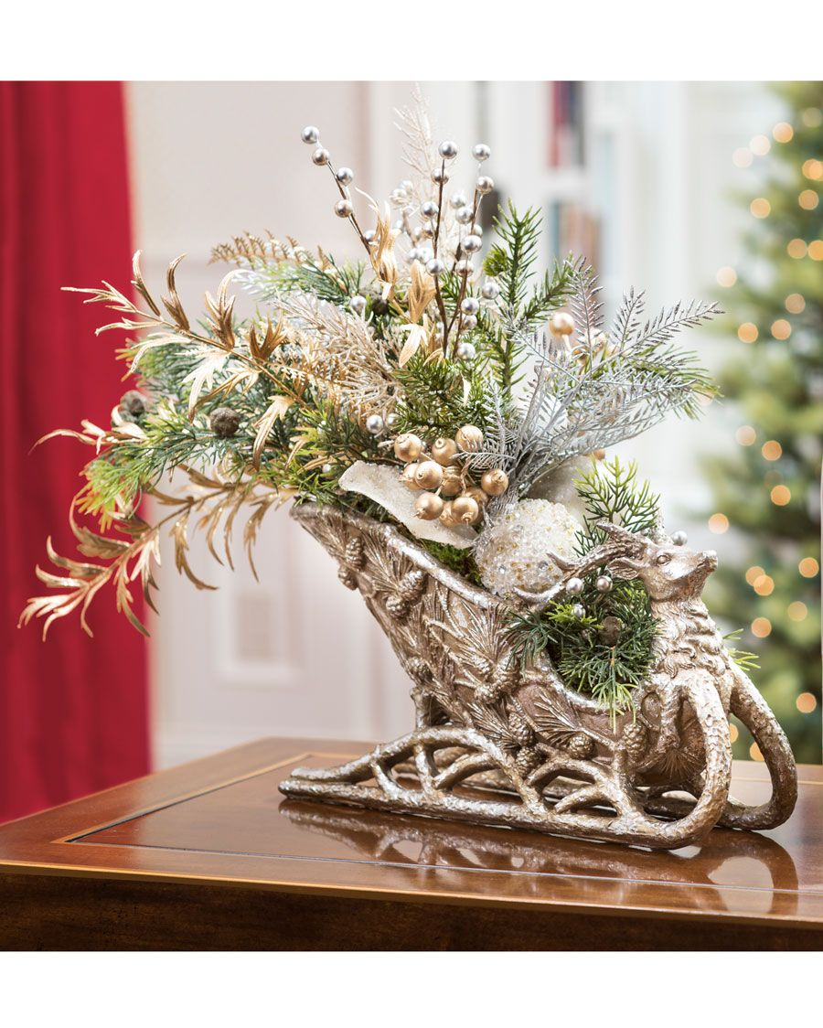 """{$tab:description} Catch their imagination Our holiday sleigh centerpiece is loaded with glistening seasonal foliage and pearlescent ball ornaments. Decorate your table with a centerpiece of elegant beauty and whimsical style designed in an antique gold and silver 14"""" resin reindeer sleigh. Make this artificial centerpiece part of your holiday decorating tradition; it will delight year after year. {$tab:DETAILS}  16"""" Height x 20"""" Width Resin Reindeer Sleigh - 7""""H x 4.5""""W x 14""""L Elegant ..."""