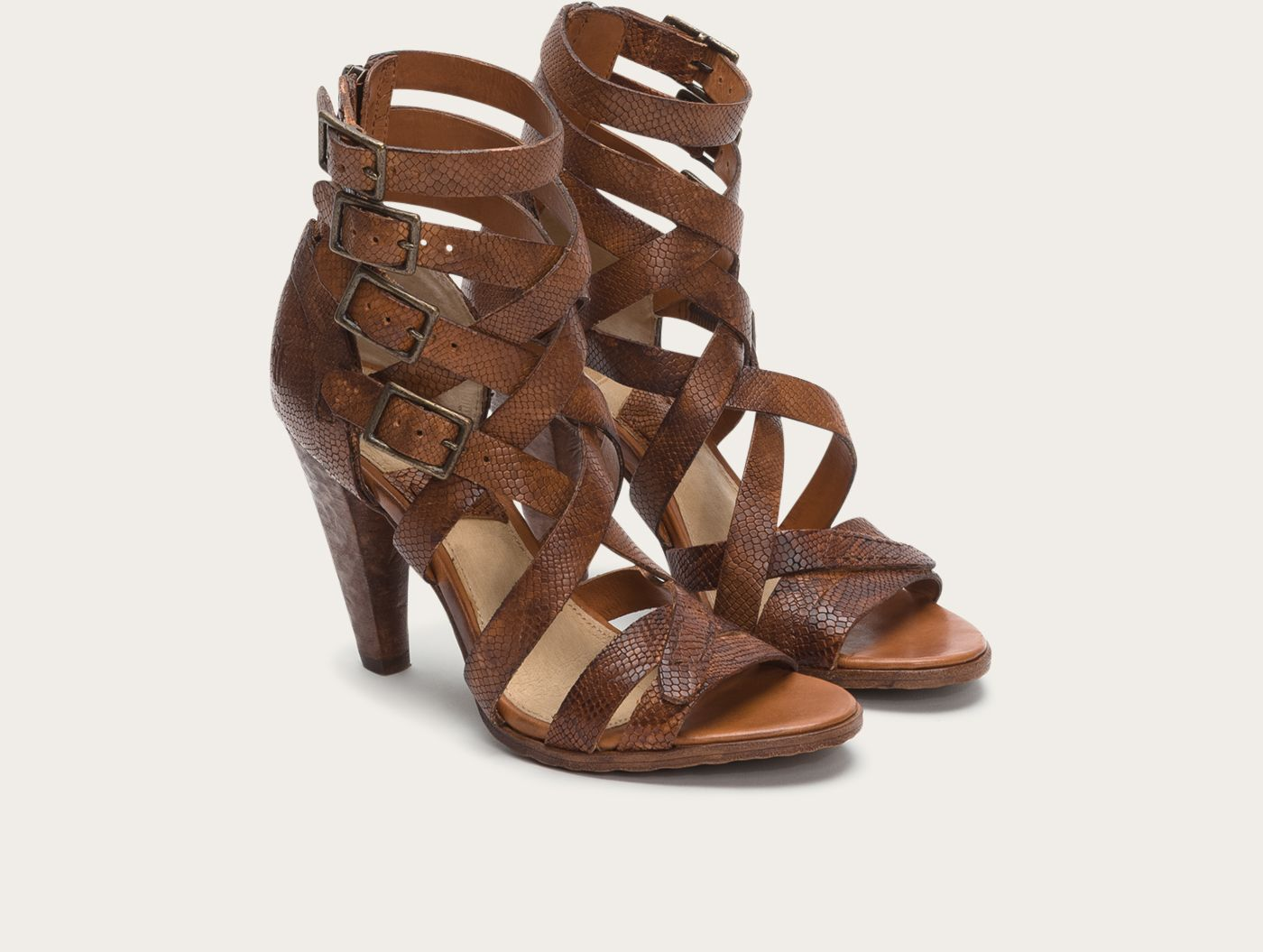 With its textured, carved heel and dramatic style, this strappy criss-cross sandal makes quite a statement. The intricate play of vintage leather straps are embossed with a subtle snake design and anchored with hand-hammered buckles. A sandal that's been known to stop traffic and steal scenes.