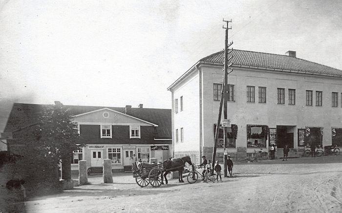 Kauniaisten keskustaan rakennettiin ensimmäinen kivinen liiketalo vuonna 1927. Itkosen liiketalossa oli myymälöiden lisäksi Kauniaisten elokuvateatteri. Rakennus purettiin vuonna 1964. Kuva on otettu 1930-luvun alussa. Nyt paikalla on kerrostalo As. Oy. Säästörata.  KAUNIAISTEN PAIKALLISHISTORIALLISEN ARKISTON KOKOELMA.