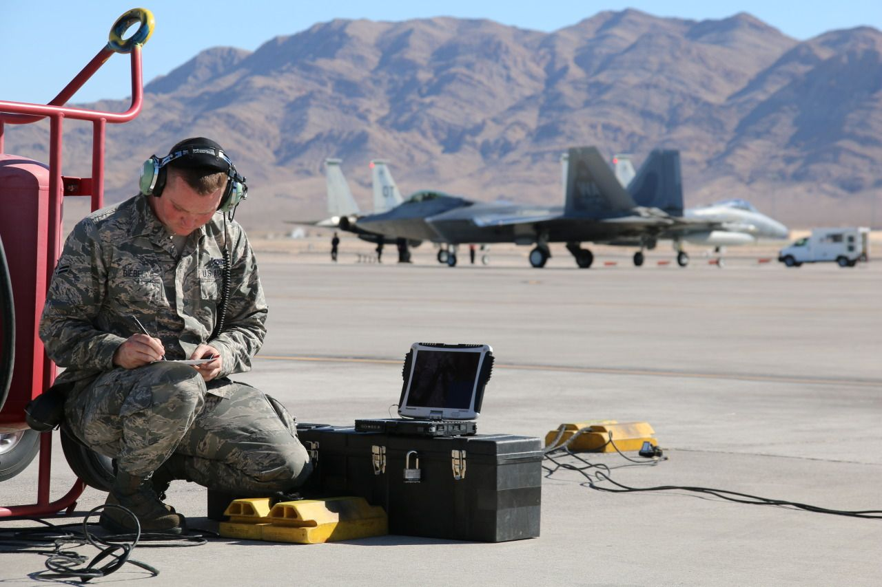A 177th Fighter Wing Airman Looks Over Technical Data While An F 22 Raptor Taxis In The Background Fighter Airman Photo