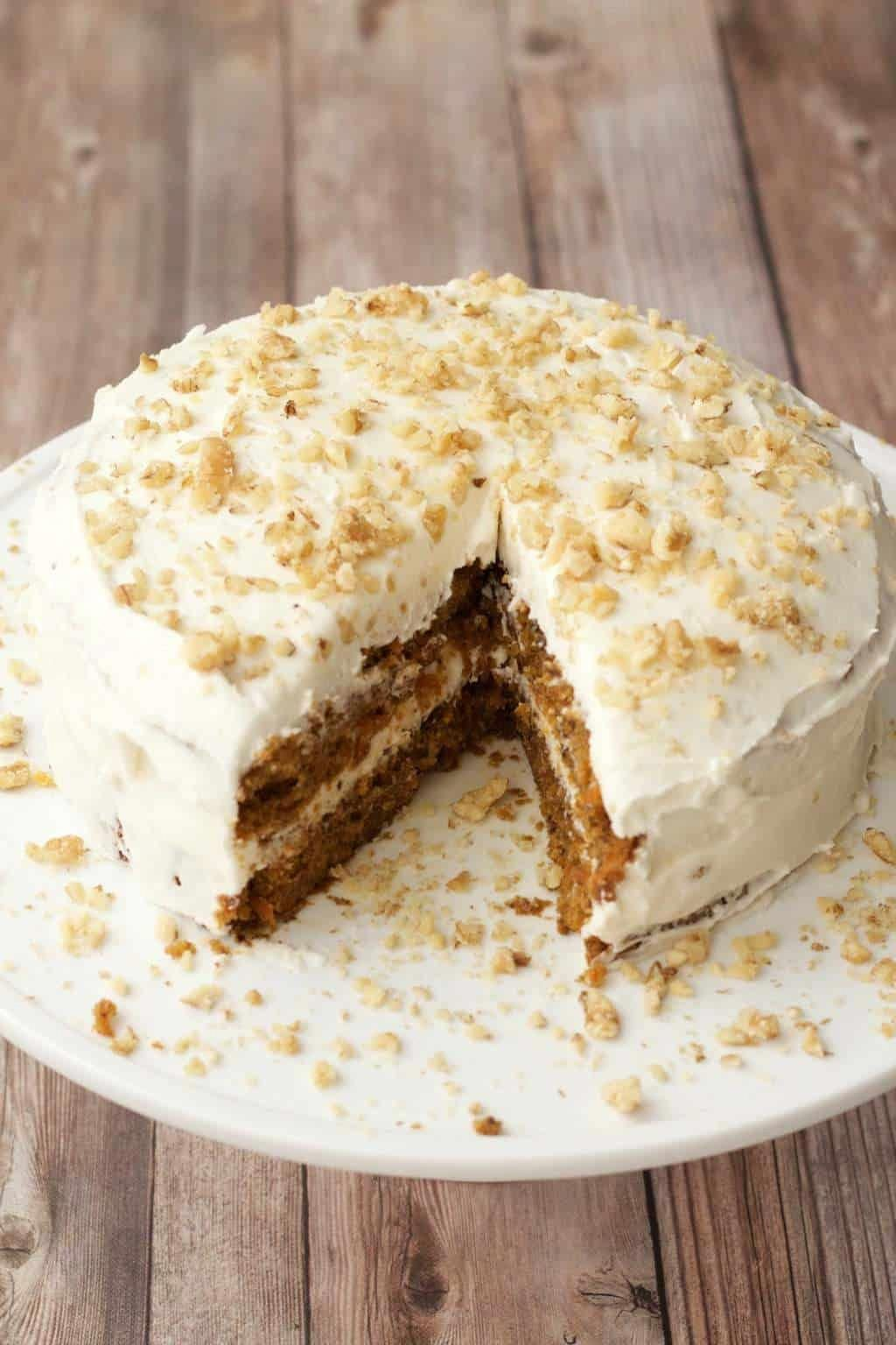 Moist, rich vegan carrot cake with a wholesome flavor and gorgeous color. Topped with lemon buttercream frosting and crushed walnuts. | lovingitvegan.com #carrotcake #lemonbuttercream