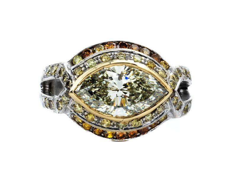 Ringweite: 54. Gewicht: ca. 8,2 g. WG 750. Aparter Ring mit zentralem Diamant im Navetteschliff, ca. 2,74 ct M/ VS, flankiert und umrahmt von kleinen gelben und...