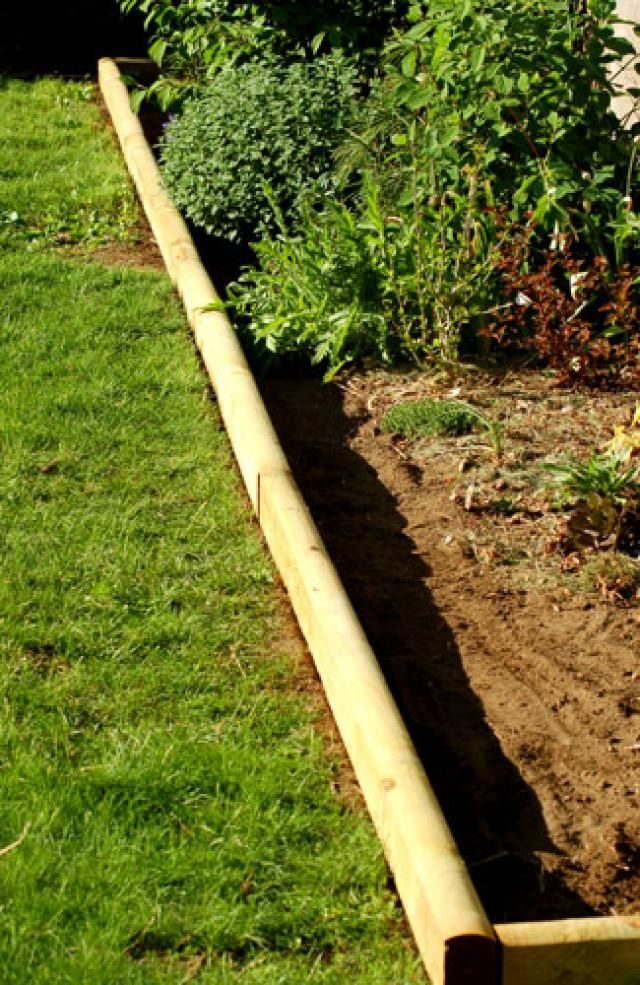 Finish off flower beds in style with landscape timbers for Cheap and easy flower bed borders