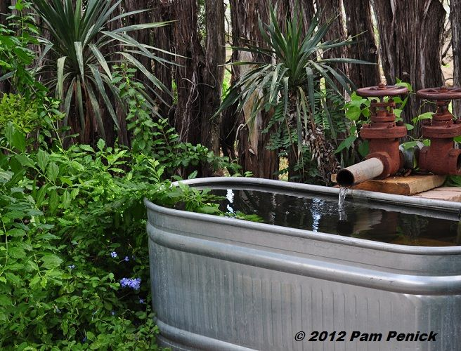 A Fountain Made Of An Industrial Looking Steel Pipe And A