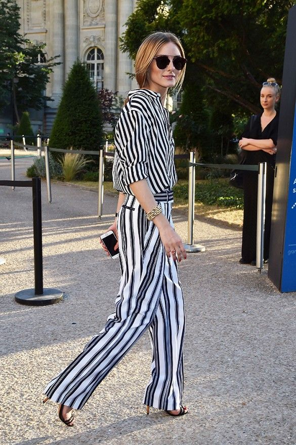 Olivia Palermo is wearing a black and white pinstriped blouse tucked into  striped trousers, black