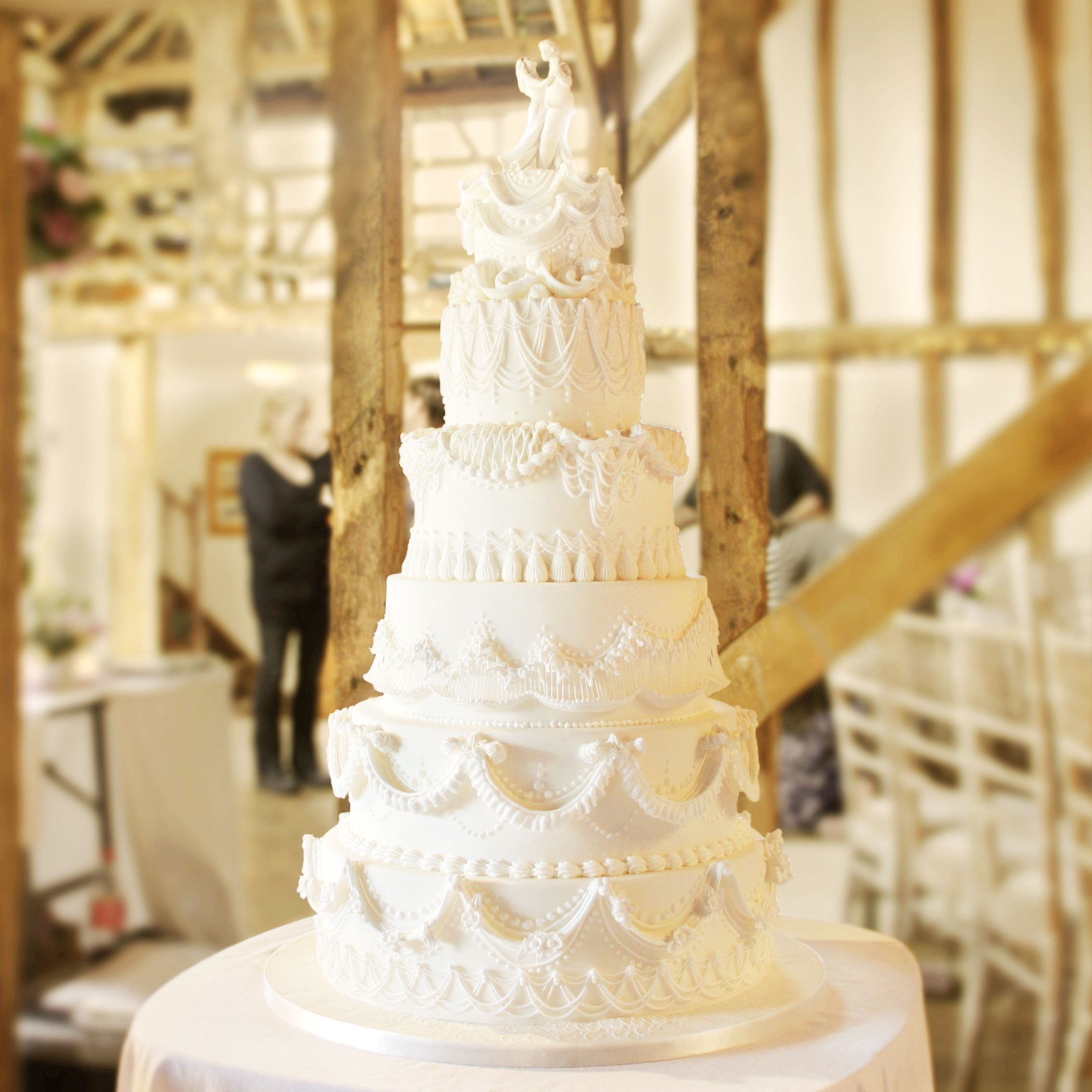 A Stacked Six Tier Wedding Cake Decorated With Variety Of Royal Icing Piping Techniques