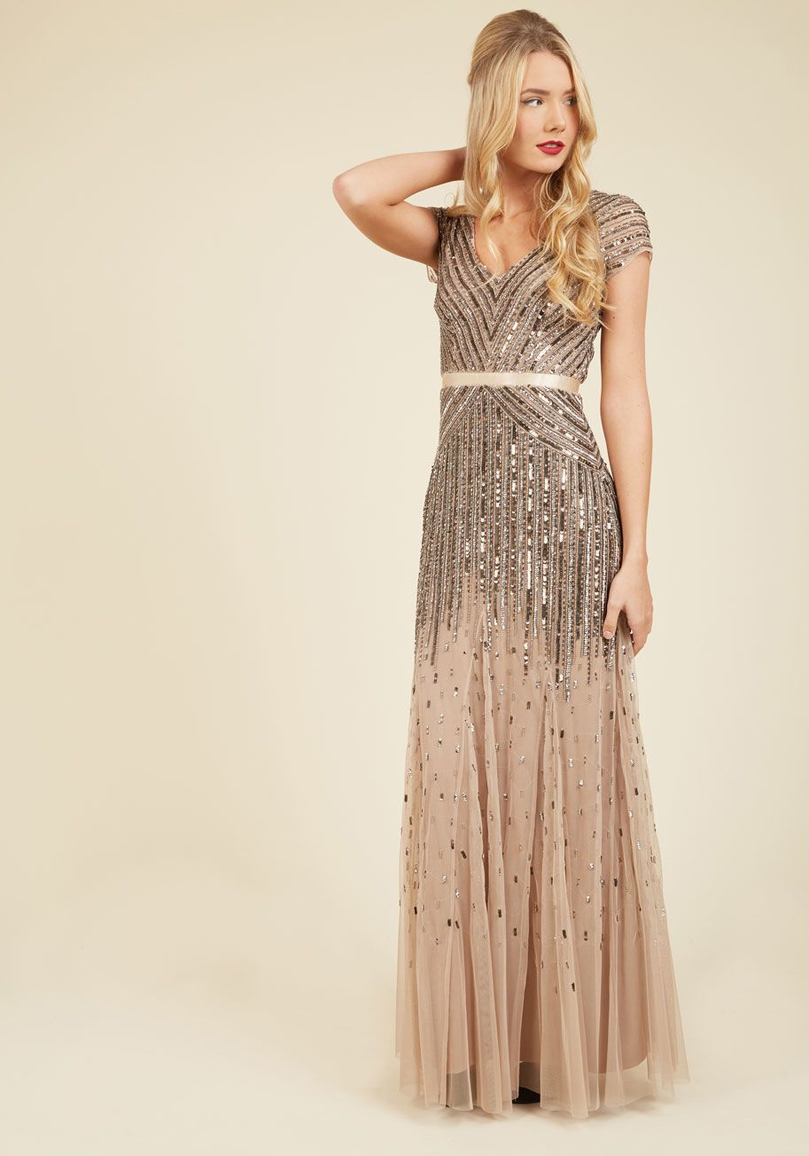 8140a4cbd2509 ... the stage in this taupe gown from Adrianna Papell. The crowd hushes as  the spotlights glisten off the cascading beads and sequins adorning this V- neck ...
