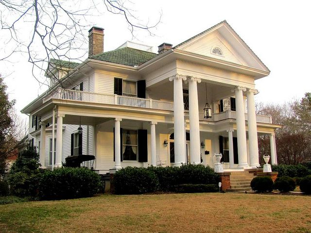 Lassiter House-. This 2 1/2 story home still has the original green tile on the roof. Topping it is a small widow's walk. The most noticeable feature is the 2-story portico with projecting pediment, supported by Ionic columns. Between the tall columns and the entrance are a row of smaller one-story Ionic columns providing the front porch area.