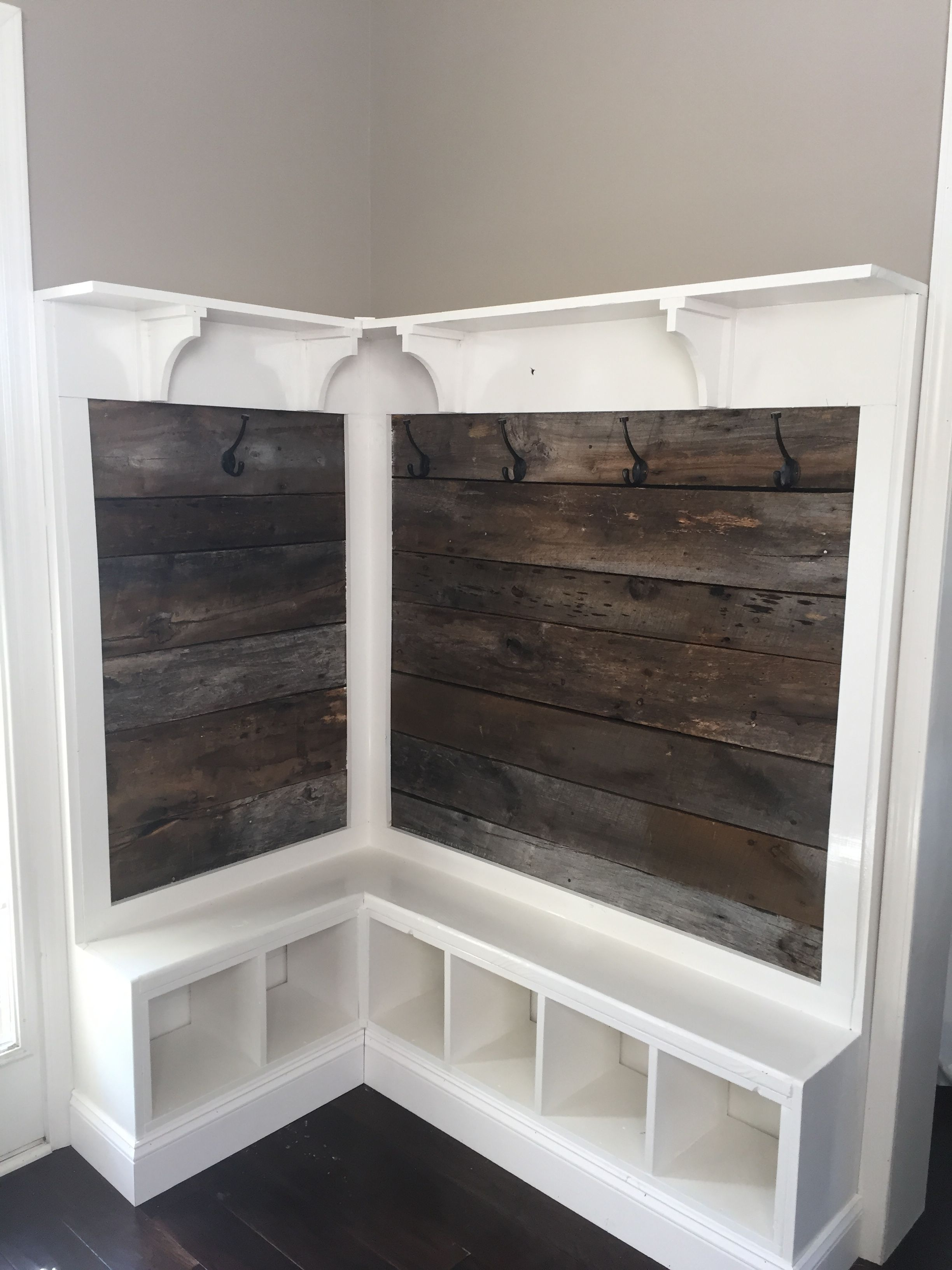 Rustic wood panel storage space for a mud room.