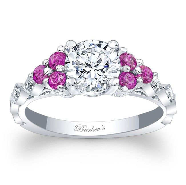 This unique diamond engagement ring features a cathedral shank with a prong set round diamond center embellished with pink sapphires on the shoulders and diamonds on the shank for a touch of elegance.<br />  <br />  Also available in yellow, rose gold, 18K, Platinum.