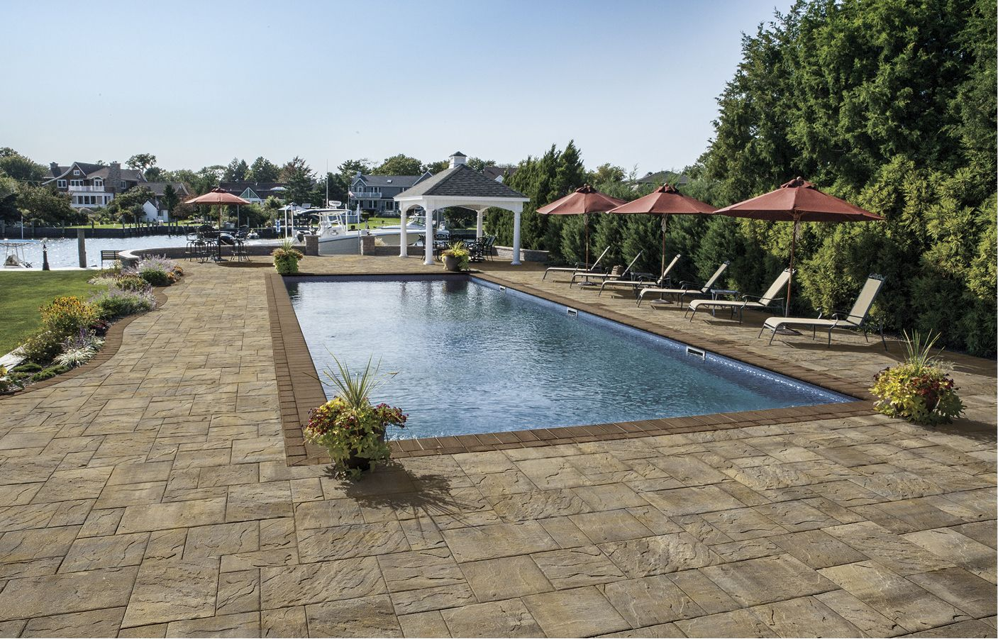 The pavingstones used to create this pool patio are The Sherwood Collection, Ledgestone Xl 3-Pc. Design Kit in Sahara/Chestnut.