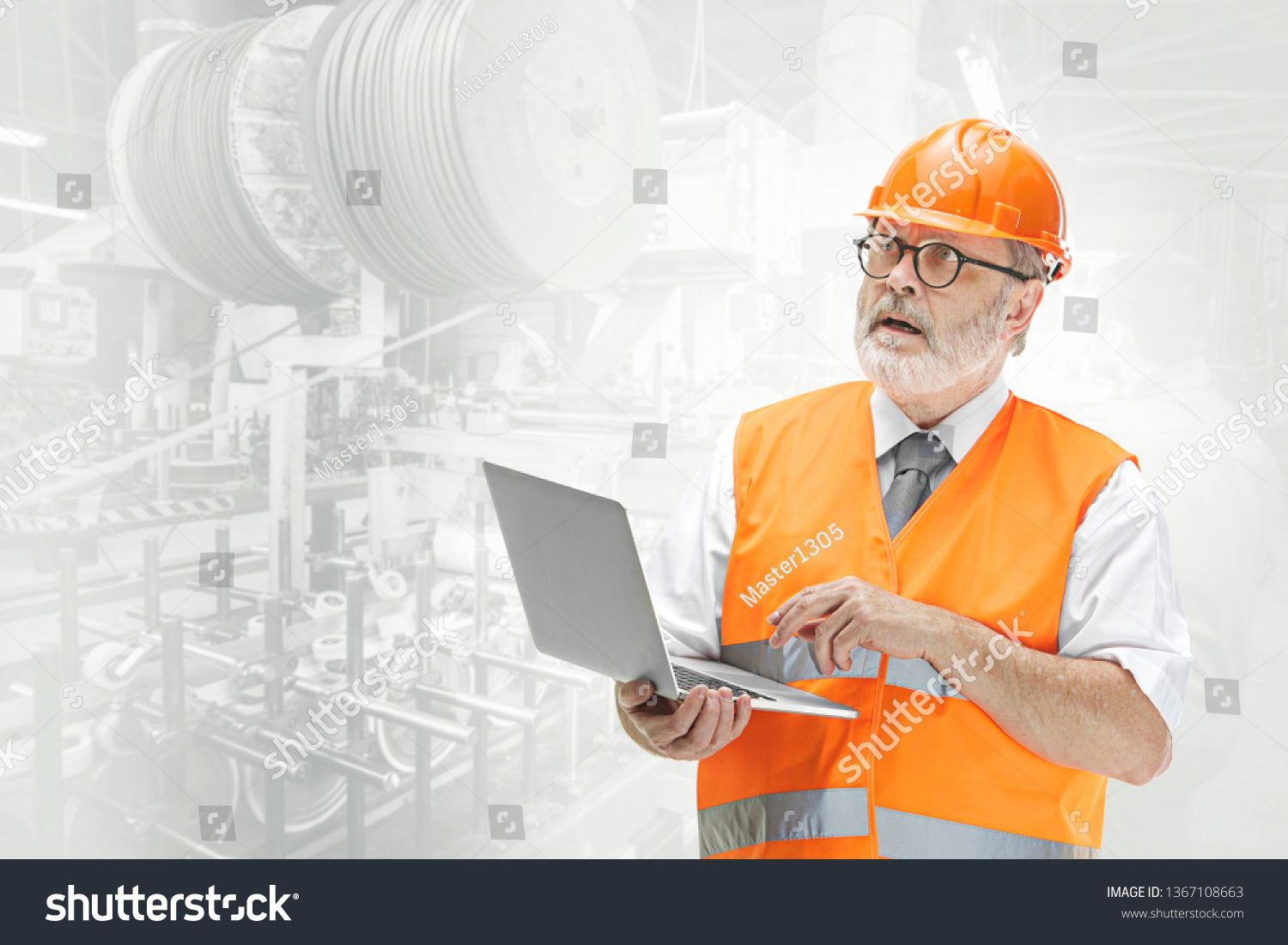 The builder in a construction vest and an orange helmet