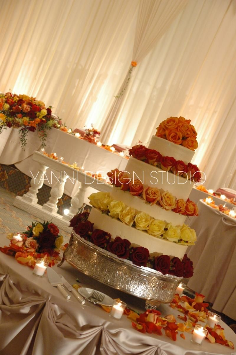 Different complementary, colored roses line each tier of the cake ...