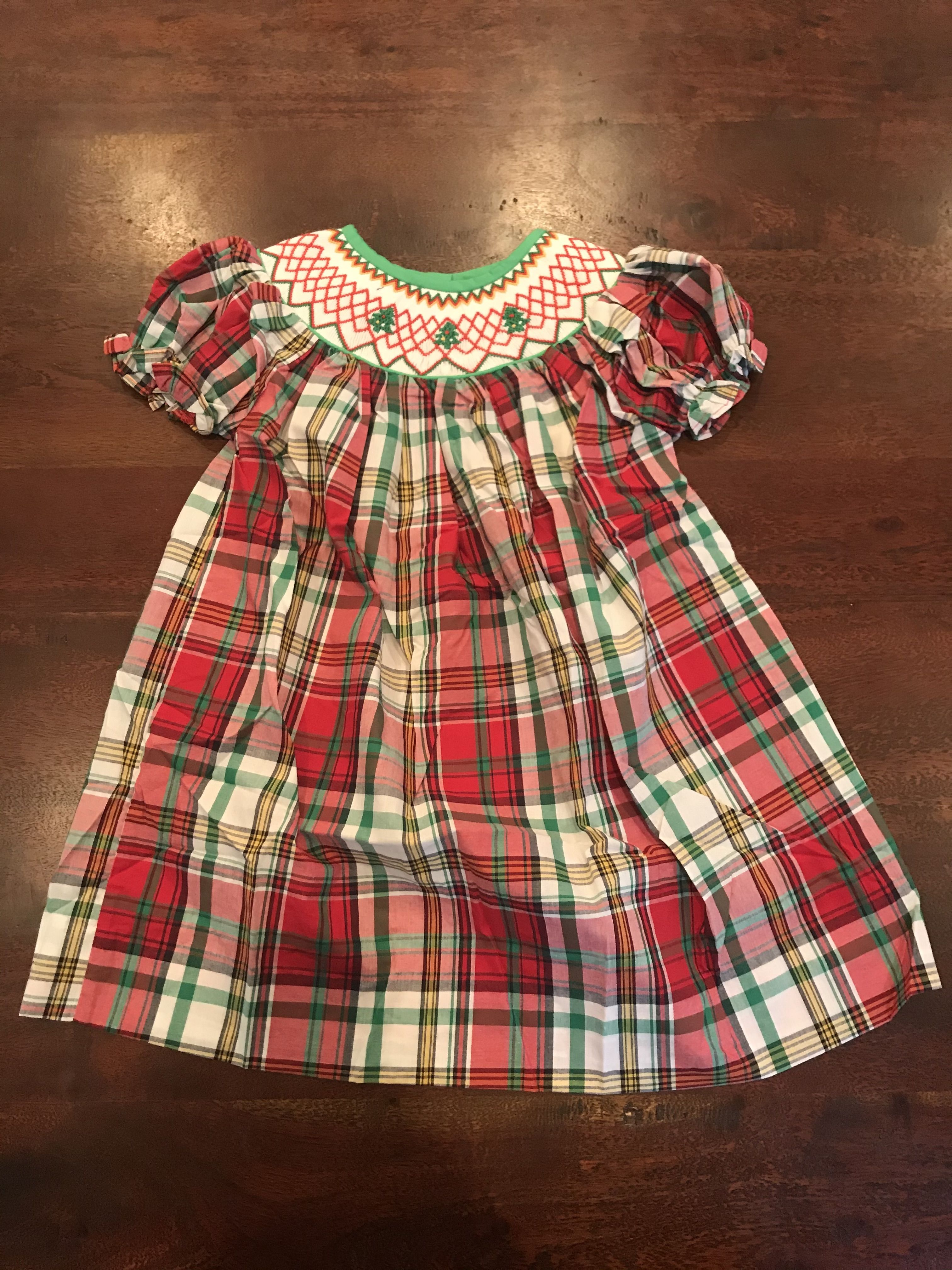 New for Fall! A holiday classic - this red plaid with intricate Christmas Tree detailing will be perfect for family photos and get-togethers this season! Multiple sizes available. Visit britchesandbows.com to shop today!  #babeeni #christmastree #christmasdress #plaiddress #redplaid #plaid #smocked #smockedchildrensclothing #smockeddress #dress #girlsdress #smockedchristmasdress #childrensholidayclothes #girlsholidayclothes #holidaydress