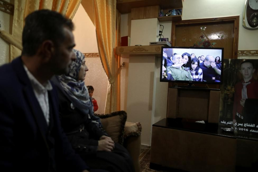 21 February 17 The parents of Palestinian Abd Elfatah Ashareef watch a TV broadcast of the sentencing hearing of Israeli soldier Elor Azaria, at their house in the West Bank City of Hebron. REUTERS/Ammar Awad