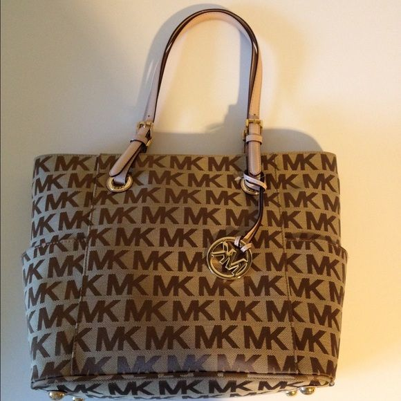 """Michael Kors Monogram Signature EW Tote NWT!! Michael Kors stylish everyday signature fabric tote. Beige/Ebony/Gold. Leather trim. Double handles with 8"""" drop. no closure. 2 open side pockets. Interior features center divider zip compartment; back zip pocket; two slip pockets; cell phone pocket; key fob. MICHAEL Michael Kors Bags Totes"""