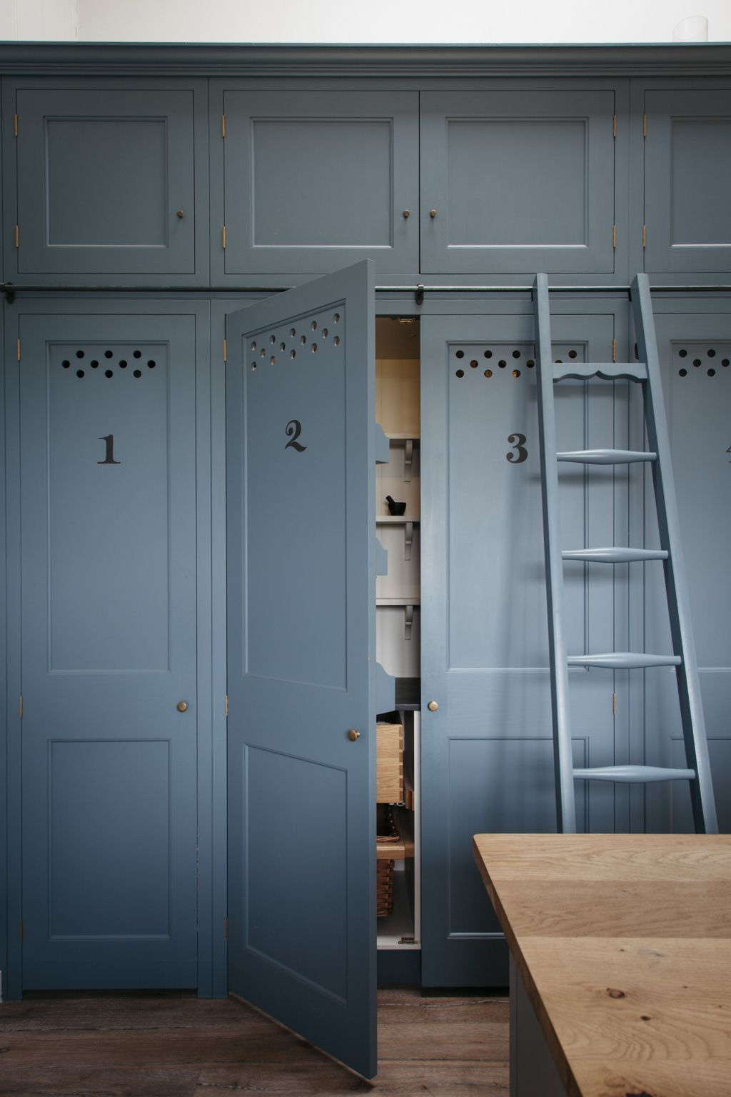 kitchen of the week the plain english power in numbers kitchen numbered kitchen cabinets with ventilation holes and a rolling ladder in a dorset farmhouse kitchen by
