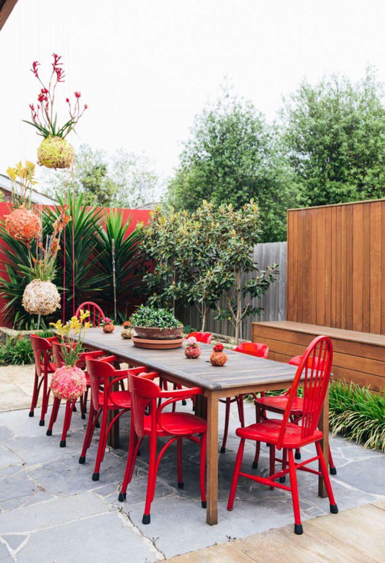 Une terrasse qui mêle meubles en teck, chaises rouges et ...