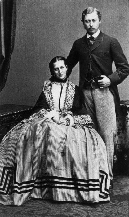 A nicely dressed couple. The bold graphic quality of her skirt trim is quite different from the decoration on her jacket or mantle.