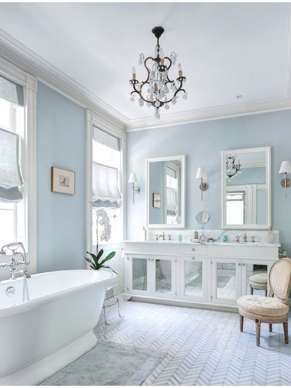Gallery For Website A white bathroom with pale blue walls a mirrored vanity and a herringbone tile