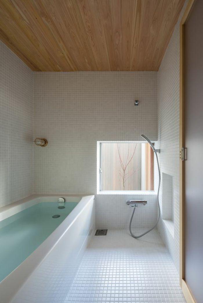 Badezimmer mit eingebauter Badewanne, weißen Fließen, viereckigem ...