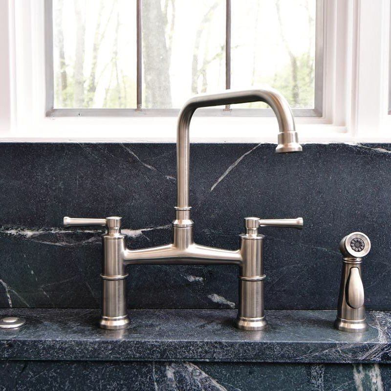 The Artesso Bridge faucet in Stainless exhibits warm artisanal ...