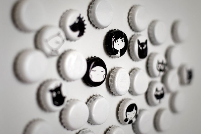 Tapas de botellas: 'First we sprayed white color on the caps and afterwards we drew some faces on them. On the other side we glued cupboards and magnets.'