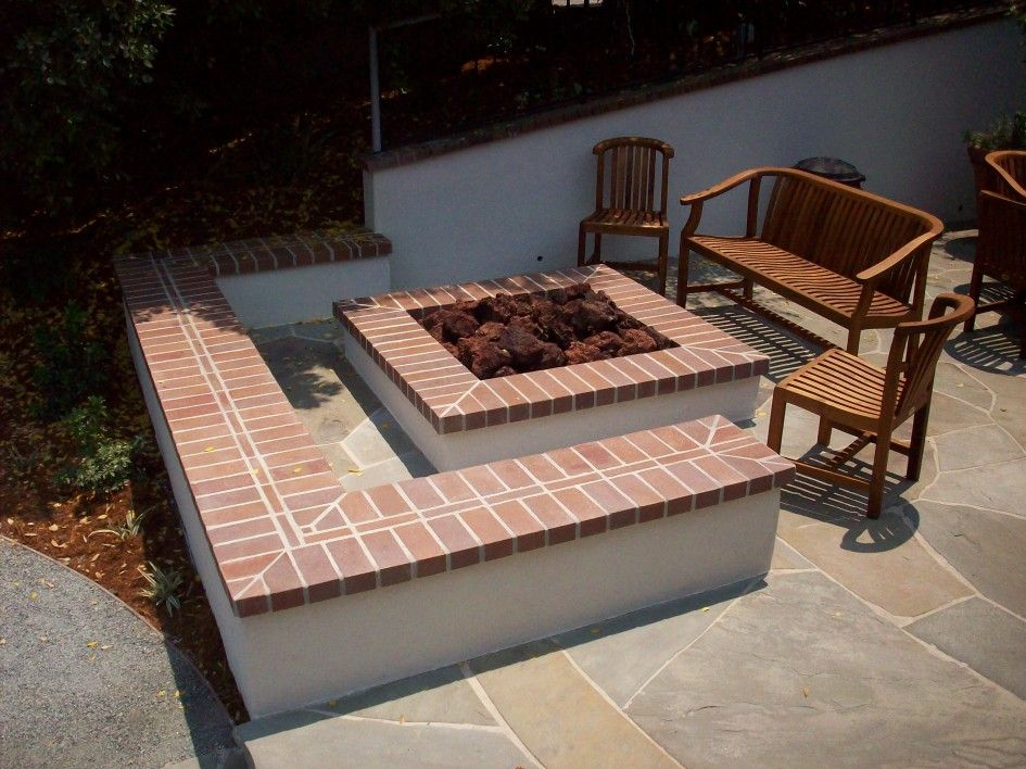 Brick Patio Wall Designs circular brick patio stands over pebble bed with brick wall surrounding elevated patterned space Simple Cute Red Brick Patio Designs Above Sand Textured Retaining Wall And Square Outdoor Fire Pit