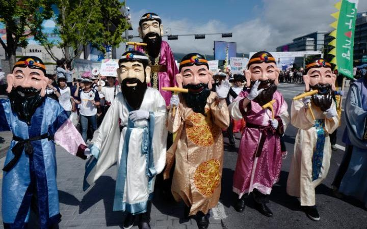 South Koran people walk while wearing the Dangun mask, made in the image of the legendary founder of Gojoseon (the first Korean kingdom), during a commemorative event marking National Foundation Day in Seoul, South Korea. National Foundation Day marks the establishment of the first Korean state of Gojoseon in 2333 BC.