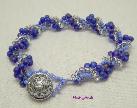 Great blue jean bracelet in blues and silver glass bead woven spiral with a beautiful lacy antique metal button