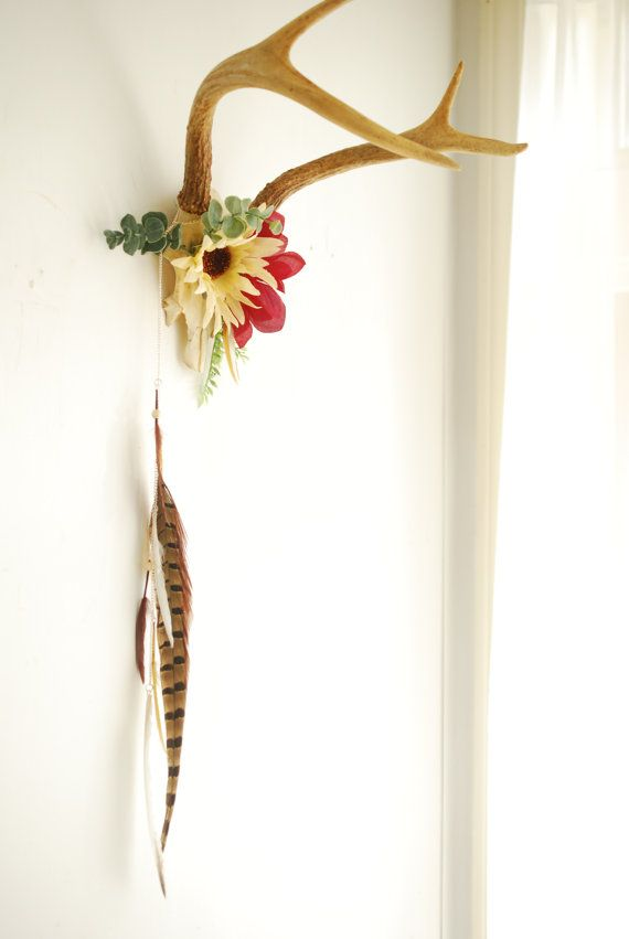 antlers flowers & feathers handmade: a set of vintage 4 point deer antlers skull mount partially covered in ivory sunflower and deep red flower surrounded by dangling white beaded feathers and striped pheasant feathers hangs simply with bracket on back *an original handmade hunterdear design* like everything in nature, nothing is perfect - please note that the antlers may be different heights/worn/weathered/cracked approx. measures: antler basket long (includes feathers & cord)