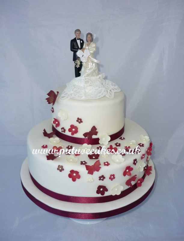 Ivory iced wedding cake decorated with shades of burgundy flowers and butterflies, two tier.