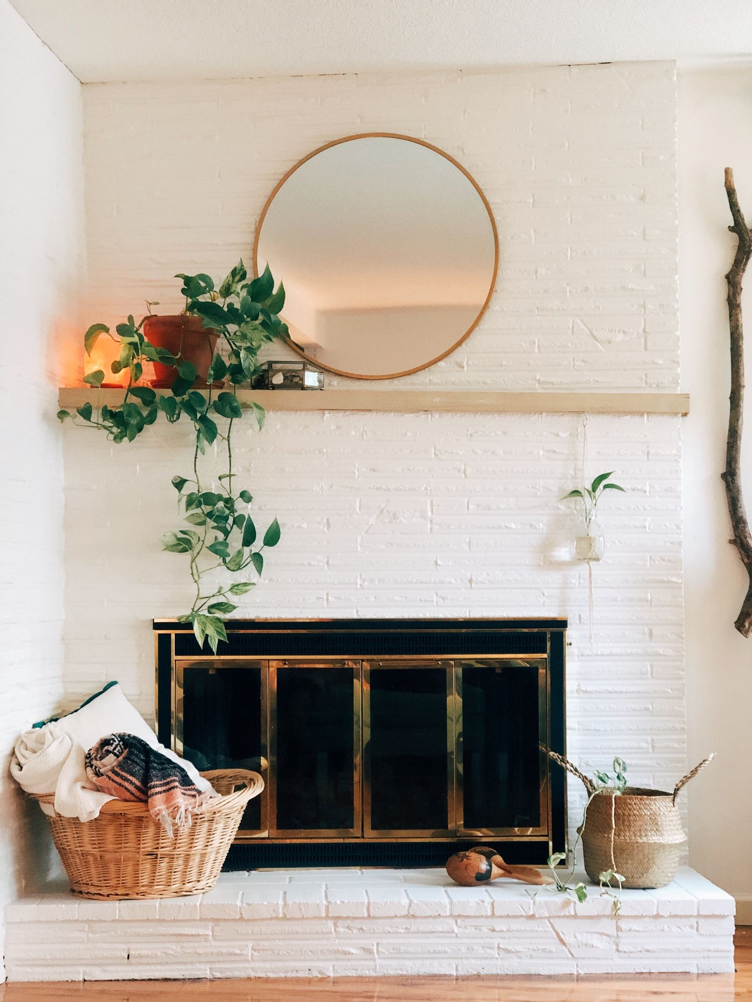 A fresh modern, cozy, boho update to this Midcentury modern white painted brick fireplace and mantle included adding a large round brass mirror, a plant, minimal mantle decor, and baskets and blankets to add texture and coziness. #whitebrickfireplace