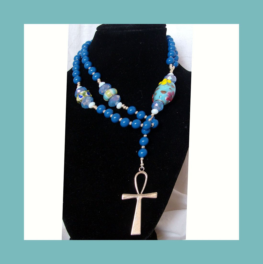 """This sweet """"Rosary Style"""" necklace has 5 decades, delineated by pastel Pandora-style beads and ending with a large Easter Egg looking Pandora style bead. Pendant is a 2"""" silver ankh, Blue beads are enameled plastic. These are one of the few types of plastic beads I will use. I just think the enameling is just so neat. Necklace is 25 inches in length, with an additional 6 inches for the pendant part. $28 Free Shipping.  Earrings and/or bracelet available for additional cost."""