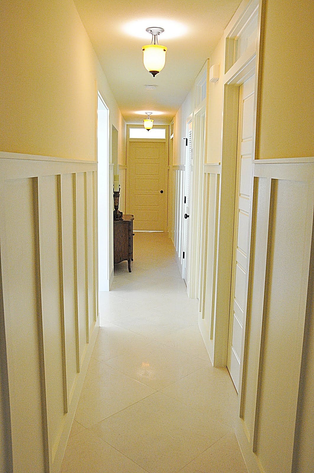 Long hallway with transom windows above the bedroom doors and board ...