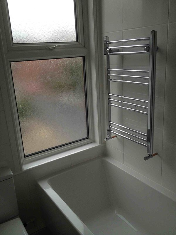 Small towel radiator over bath in a bathroom installation for How to heat a small bathroom