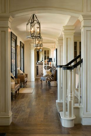 Joy Tribout Interior Design- gorgeous neutral entry! So many favorites, staircase, moldings on pillars, flooring, black windows, archway, french doors more on http://idesigninterior.net