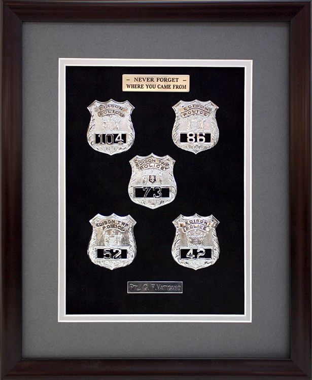 Police badges displayed in dark wooden frame with silver accent ...