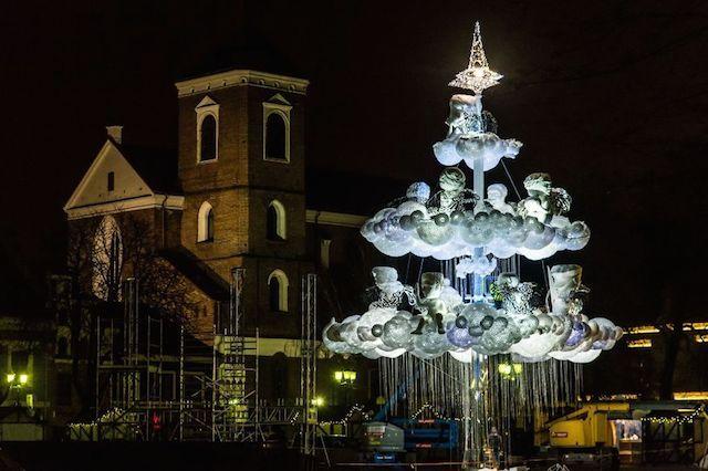 """Como nos anos anteriores, os artistas da cidade de Caunas, na Lituânia, tem pensado na mais nova árvore natalina desse ano. A criativa tradição que já ocorre há anos tem como objetico criar uma árvore que seja diferente das árvores tradicionais. Neste ano foi feita uma árvore totalmente iluminada, no formato de nuvens """"mágicas"""" e decorada com dúzias de esculturas de anjos com um estilo contemporâneo."""