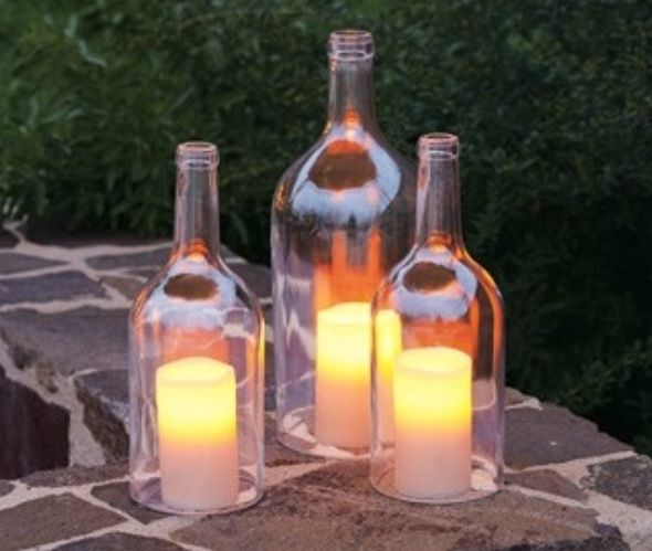 Cut the bottoms off wine bottles and place over candles to stop the wind blowing them out ... So easy and cheap
