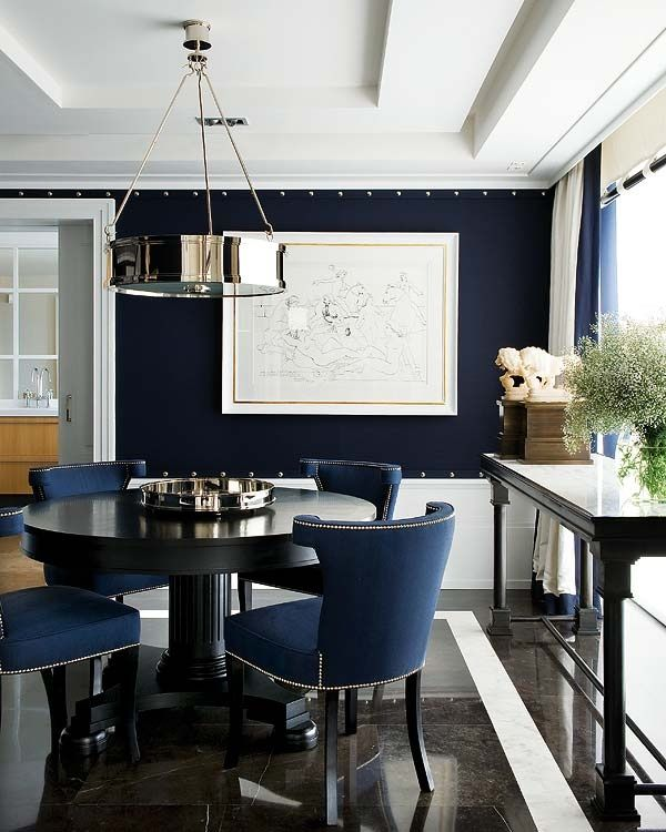 Daringly dark upholstered walls, a lovely round dining table with ...