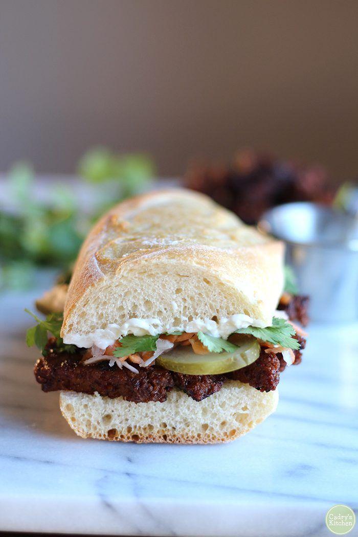 Vegan banh mi sandwich with seitan on white cutting board.