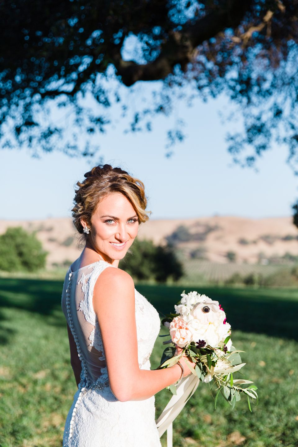 Bridal pose with flowers looking over the Los Olivos hillside at the Firestone Vineyard and Winery.