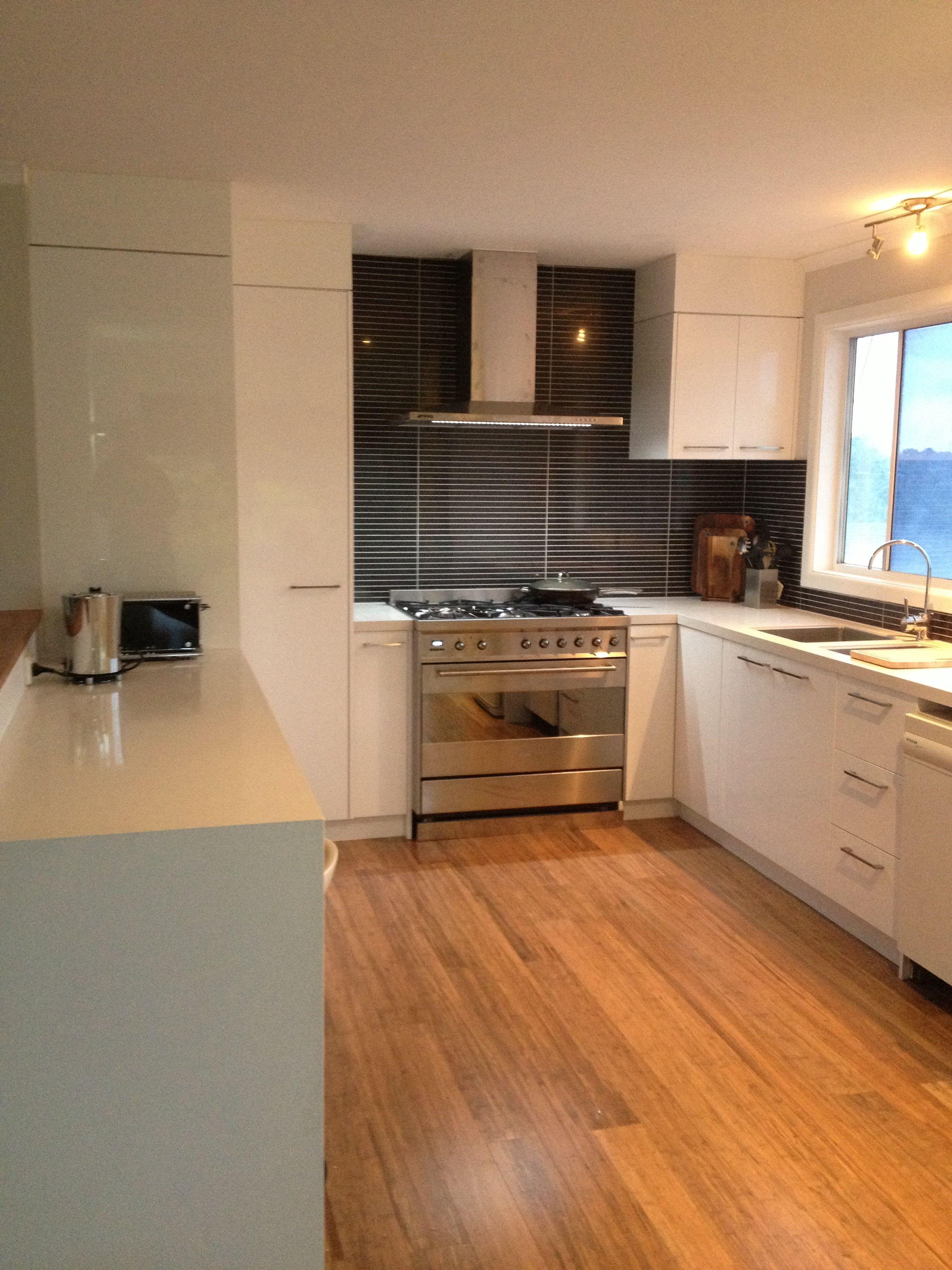 White gloss kitchen, bamboo floor, tile splash back