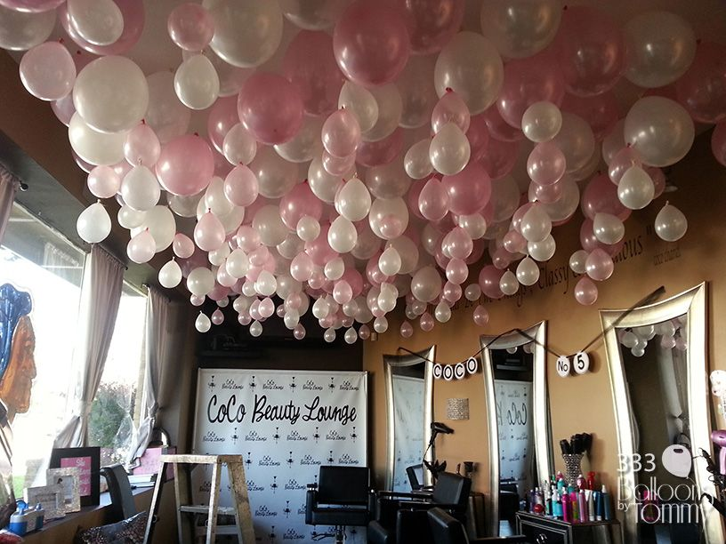Pink and white balloons fill the ceiling for a grand for Balloon decoration for ceiling