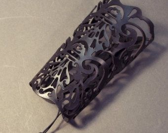 A filigree Victorian style cuff delicately cut from veg tan leather, then painted purple. Fits a 5¾ wrist or larger. Cuff measures 5 long. Secured by