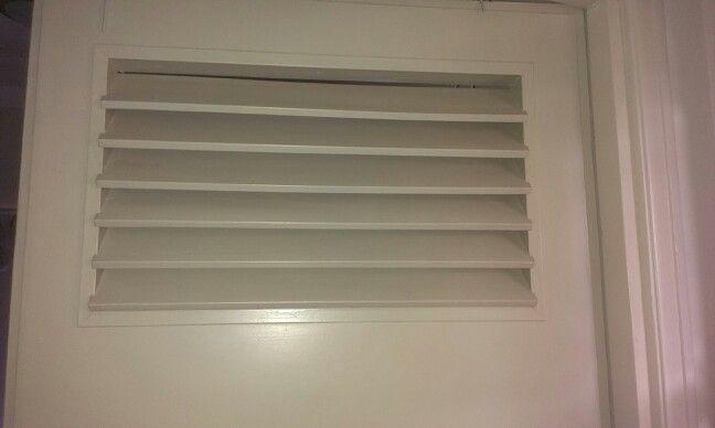 Ventilatierooster in de deur van de badkamer. Stijlvol en ...