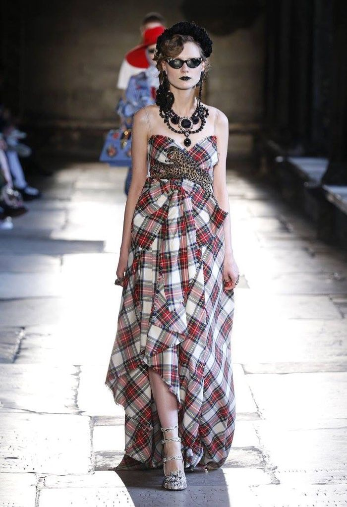A model walks the runway at Gucci's resort 2017 show wearing a tartan gown with a brooch necklace