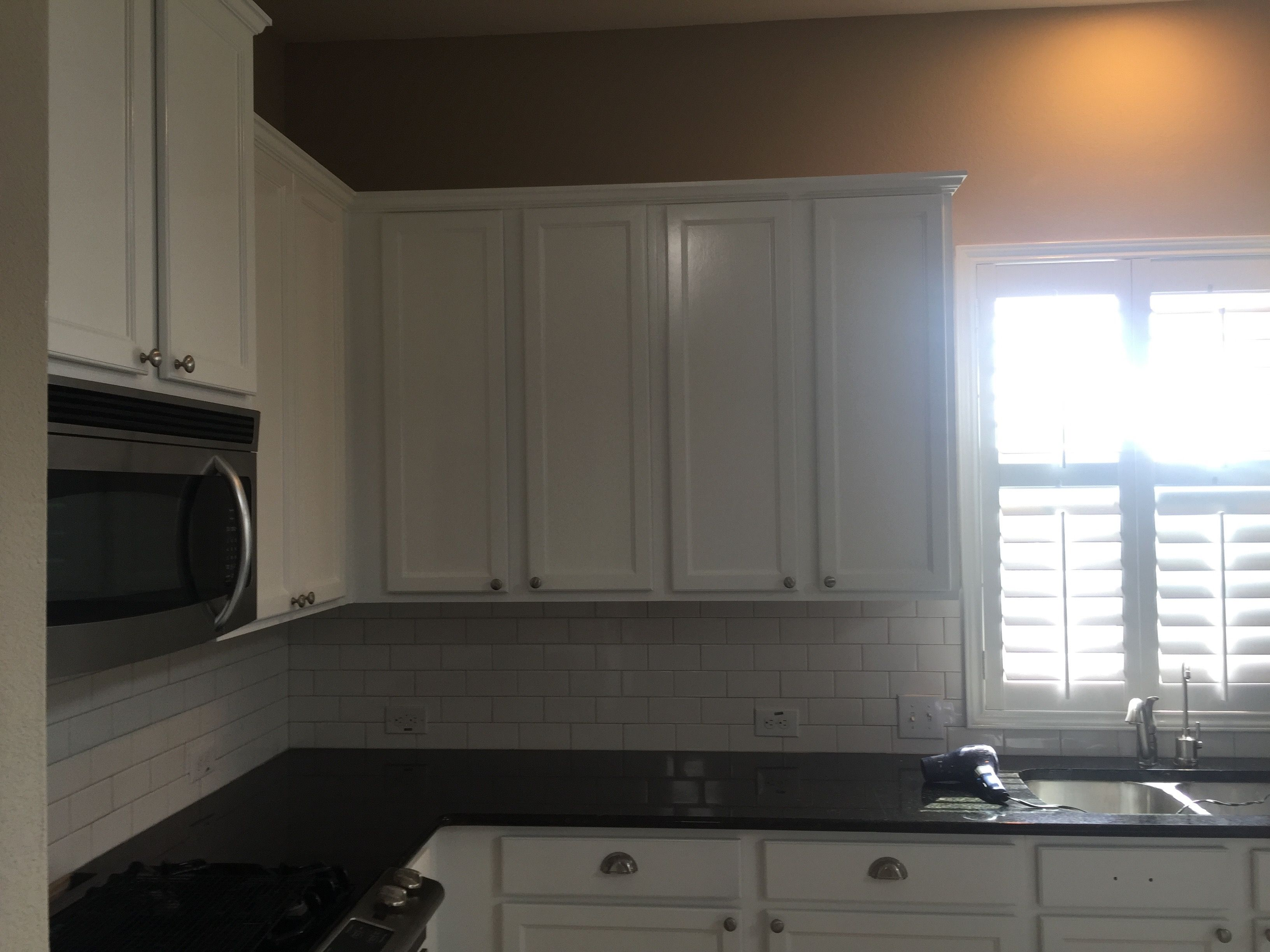 We painted these cabinets bright white and put in a new tile backsplash to give this